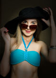 Beautiful young lady in a bathing suit, big black hat on high heels, and sunglasses Royalty Free Stock Photography