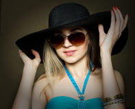 Beautiful young lady in a bathing suit, big black hat on high heels, and sunglasses Stock Photo