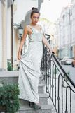 Beautiful young lady. Posing on the street near the handrail standing on the steps dressed in a long dress stock photos