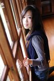 Beautiful young lady behind the wooden door Stock Image