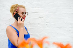 Beautiful young lady in big glasses speaking phone Stock Photo
