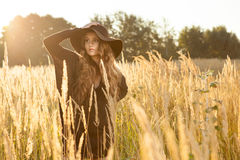 Beautiful young lady in a brown dress in a field - sunrise shot Royalty Free Stock Photo