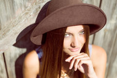Beautiful young lady in brown hat smiling beside Royalty Free Stock Photography