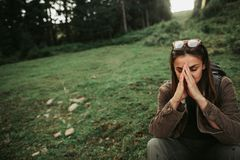 Beautiful young lady burying face in hands while sitting on grass royalty free stock photo