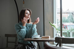 Beautiful young lady in cafe looking at mirror. Royalty Free Stock Photography