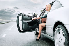 Beautiful young lady came out frome her car on the road royalty free stock images