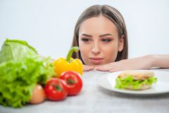 Beautiful young lady chooses between healthy and. Pretty woman is making decision to eat vegetables. She is looking at it and does not pay her attention on Royalty Free Stock Photo