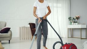 Beautiful young lady is cleaning the house hoovering floor and listening to music enjoying melody and dancing. Modern. Beautiful young lady is cleaning the house stock video footage
