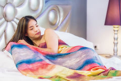 Beautiful young lady covered by Brightly colored blankets royalty free stock photo