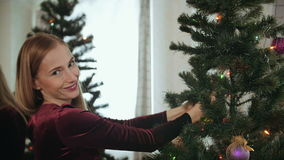 Beautiful young lady decorate the Christmas tree stock video