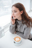 Beautiful young lady drinking coffee while talking by phone Stock Images