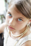 Beautiful Young Lady. Young girl looking directly into the camera, wearing vintage pearl necklace and hair pulled back. Extreme shallow depth of field with Royalty Free Stock Photos