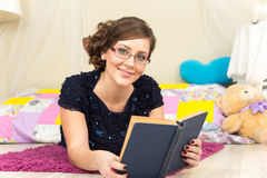 Beautiful young lady in glasses reading a book at home. Near pillows Royalty Free Stock Photography