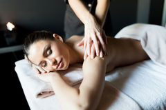 Beautiful, young lady having her shoulder and body massaged by a Royalty Free Stock Images