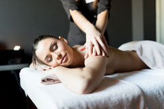 Beautiful, young lady having her shoulder and body massaged by a Royalty Free Stock Photos