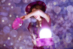 Beautiful young lady hiding from bright light in gift box Stock Photos