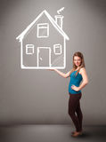 Young lady holding a huge drawn house Stock Photo