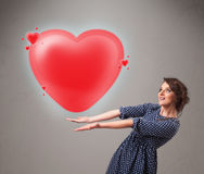 Young lady holding lovely 3d red heart Stock Photo