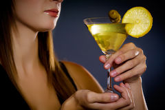 Beautiful young lady holding martini Stock Images