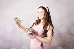 Beautiful young lady holding US banknotes and piggy bank Stock Photo