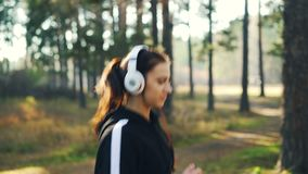 Beautiful young lady is jogging in park wearing headphones and listening to music enjoying activity and favorite song. And smiling. Nature, youth and modern stock footage