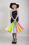 Beautiful young lady in a little blue dress on high heels, holding colorful bags. Girl goes shopping stock photos