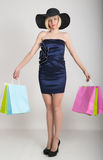 Beautiful young lady in a little blue dress on high heels, holding colorful bags. Girl goes shopping royalty free stock images