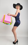 Beautiful young lady in a little blue dress on high heels, holding colorful bags. Girl goes shopping stock photo