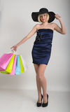 Beautiful young lady in a little blue dress on high heels, holding colorful bags. Girl goes shopping Stock Images