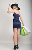 Beautiful young lady in a little blue dress on high heels, holding colorful bags. Girl goes shopping Stock Photography