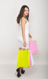 Beautiful young lady in a little white dress on high heels, holding colorful bags. Girl goes shopping Stock Images