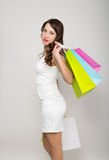 Beautiful young lady in a little white dress on high heels, holding colorful bags. Girl goes shopping Royalty Free Stock Photography