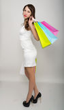 Beautiful young lady in a little white dress on high heels, holding colorful bags. Girl goes shopping Stock Photography