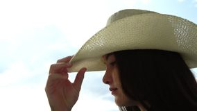 Beautiful lady with long brown hair and in white cowboy hat. Beautiful young lady with long brown hair and in white cowboy hat smiles and looks at sky extreme stock video footage