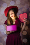Beautiful young lady looking at heart box on bokeh background Royalty Free Stock Photo