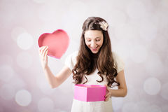 Beautiful young lady looking at heart box on bokeh background Royalty Free Stock Photos