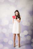 Beautiful young lady looking at heart box on bokeh background Royalty Free Stock Photography