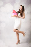 Beautiful young lady looking at heart box on bokeh background Stock Photos