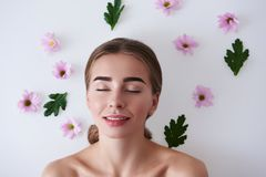 Beautiful young lady lying on white background with flowers and green leaves royalty free stock images