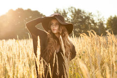 Beautiful young lady model in field at sunset Royalty Free Stock Photo