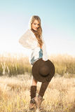 Beautiful young lady model posing in a field at sunrise with a hat in hand Royalty Free Stock Photos