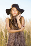 Beautiful young lady model posing in front of camera in a field at sunrise Stock Photos