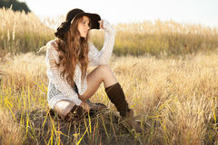 Beautiful young lady model sitting in field at sunrise Stock Images