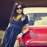 Beautiful young lady near a retro car. Royalty Free Stock Photo