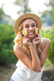 Beautiful young lady on a park background. A smiling female in a hat, holding lemons. Exotic diets. Healthy lifestyle. An attractive, smiling young female in a royalty free stock image