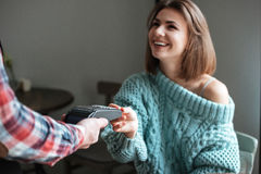 Beautiful young lady pays for her order with debit card. Royalty Free Stock Photos
