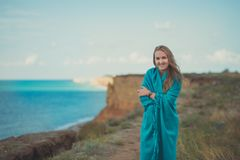 Beautiful young lady posing on marvellouslandscape of sea ocean sand cliff with colourful horizon and tiny clouds full of dreams stock images