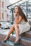 Beautiful young lady posing on the street. Against the background of the buildings sitting on the stairs dressed in a long silver dress stock images