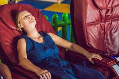 Beautiful young lady relaxing in the massage chair.  royalty free stock photos