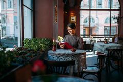 Young smiling happy woman in cafe. Beautiful young lady in retro style dress reading book. Smiling brunette in vintage dress brown color sits in cafe near window Royalty Free Stock Image